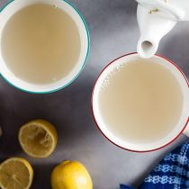 holding a mug of ginger lemon tea with a blue blanket and a teapot