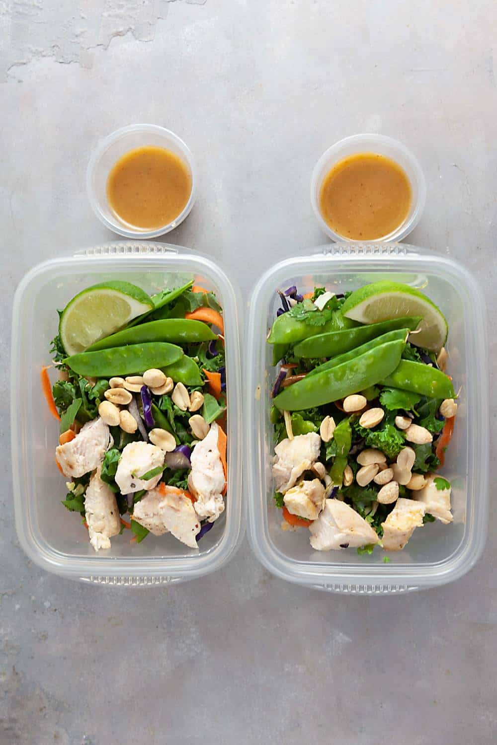 two meal prep containers filled with Thai chicken salad and peanut dressing