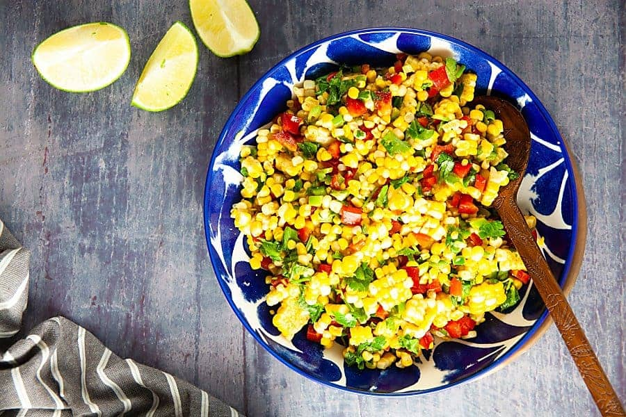 curried corn salad in a blue bowl with limes