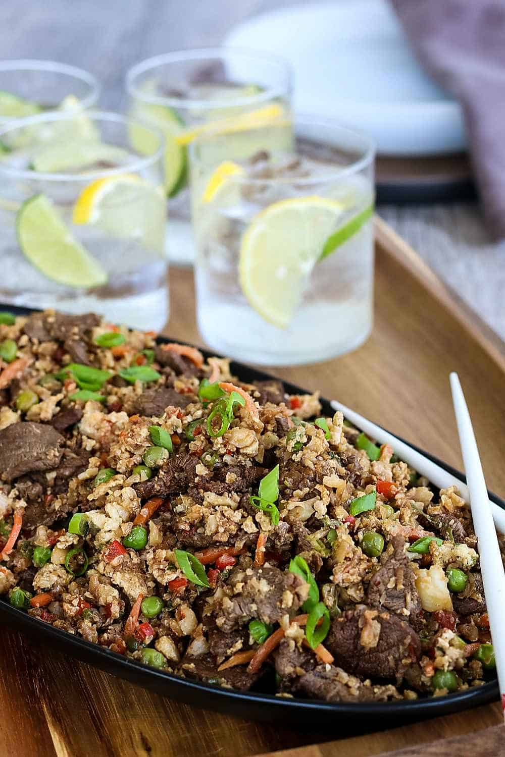 Flavorful cauliflower rice stir fry on a serving platter with drinks.