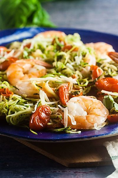 pesto zucchini noodles with baked shrimp on a blue platter