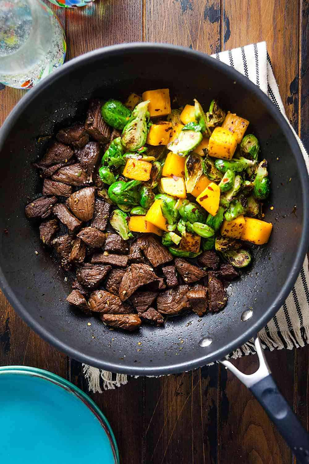 steak tips, butternut squash, and Brussels sprouts in a skillet
