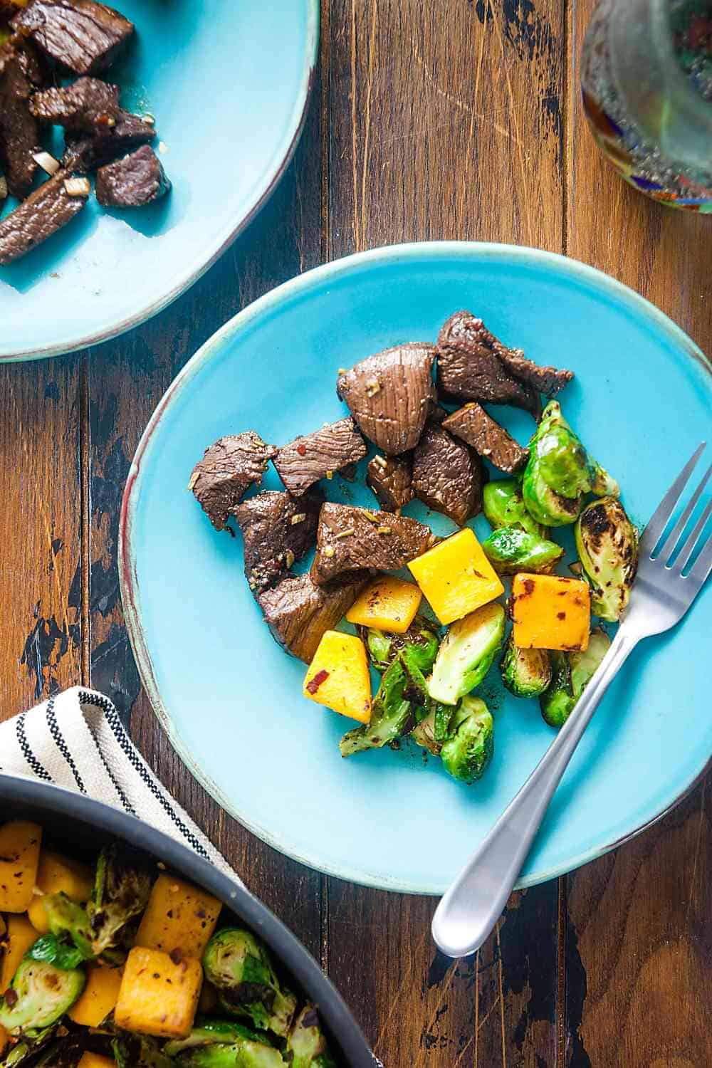 rosemary-balsamic marinaded steak tips with butternut squash and Brussles sprouts on a plate