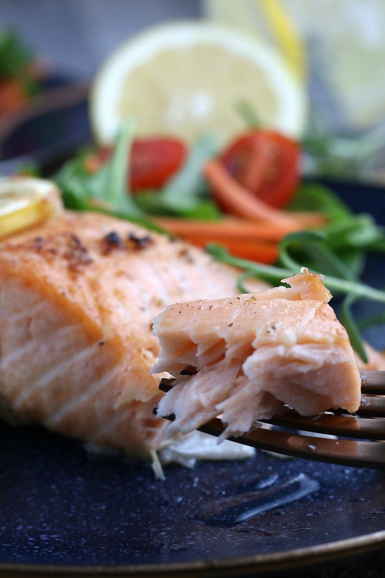 A close up view of the finished healthy salmon recipe on a fork ready to be eaten.