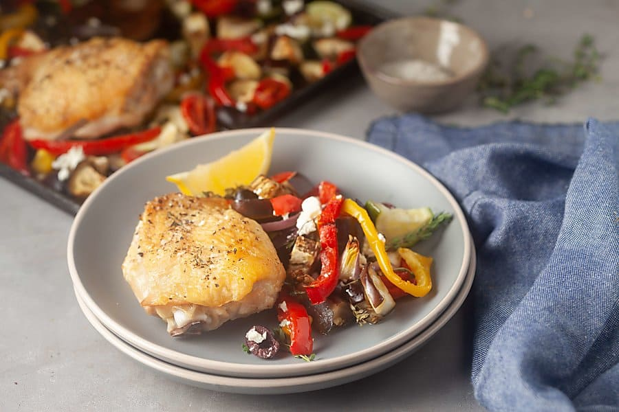Greek chicken thighs with vegetables on a sheet pan