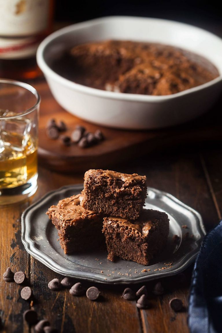 a plate of Irish whiskey brownies with a glass of whiskey and a pan of brownies behind