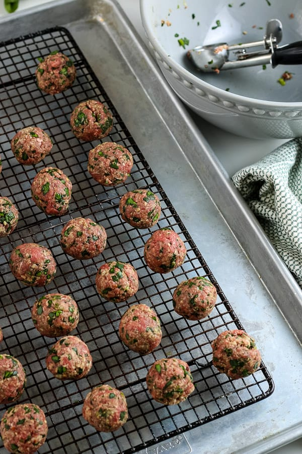 shaping homemade meatballs and placing them on a rack