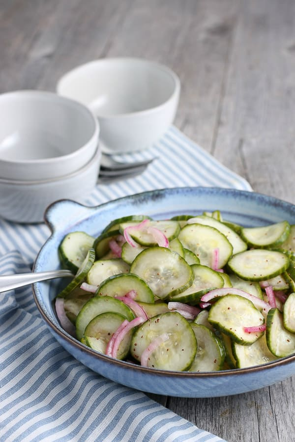 a blue bowl filled with cucumber salad