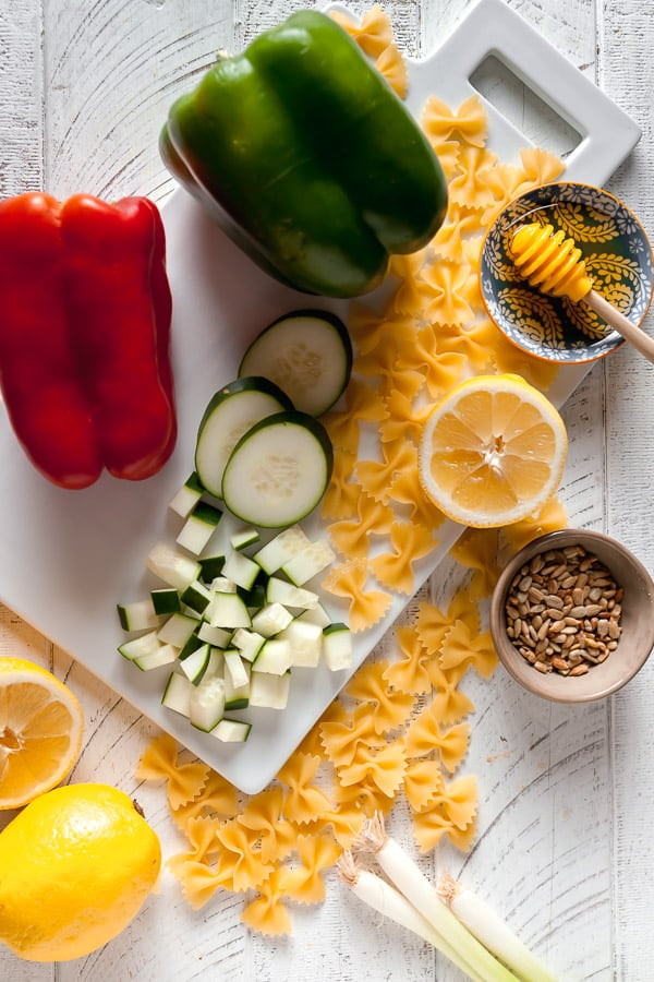 ingredients to make lemon chicken pasta salad - bell peppers, cucumbers, lemon, honey, sesame seeds, and pasta