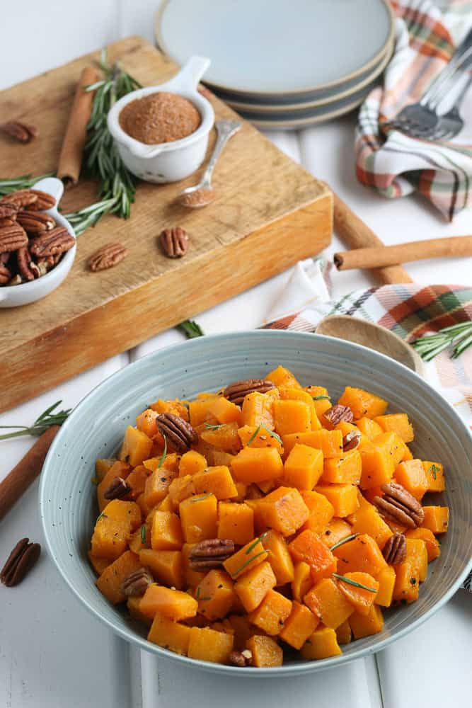 blue bowl full of roasted butternut squash cubes with ingredients in the background