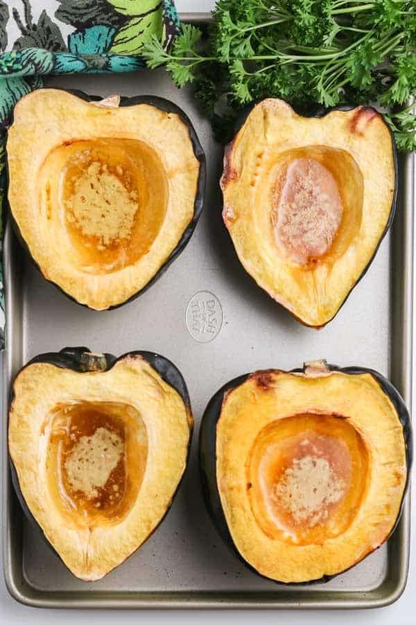 fully cooked acorn squash with pools of butter and syrup