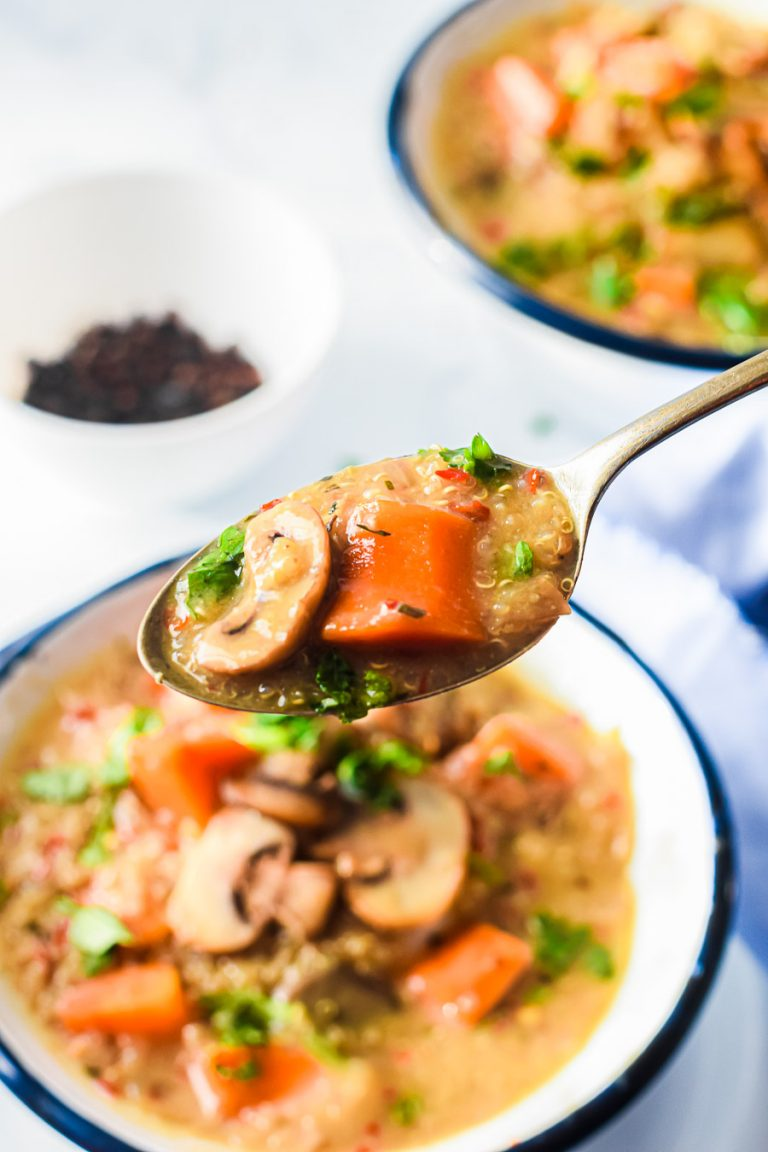 a spoon full of quinoa and mushroom soup above a bowl of soup