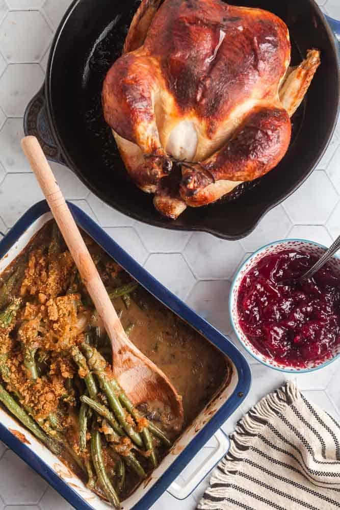 overhead view of chicken dinner with roast chicken, cranberry sauce, and fresh green bean casserole