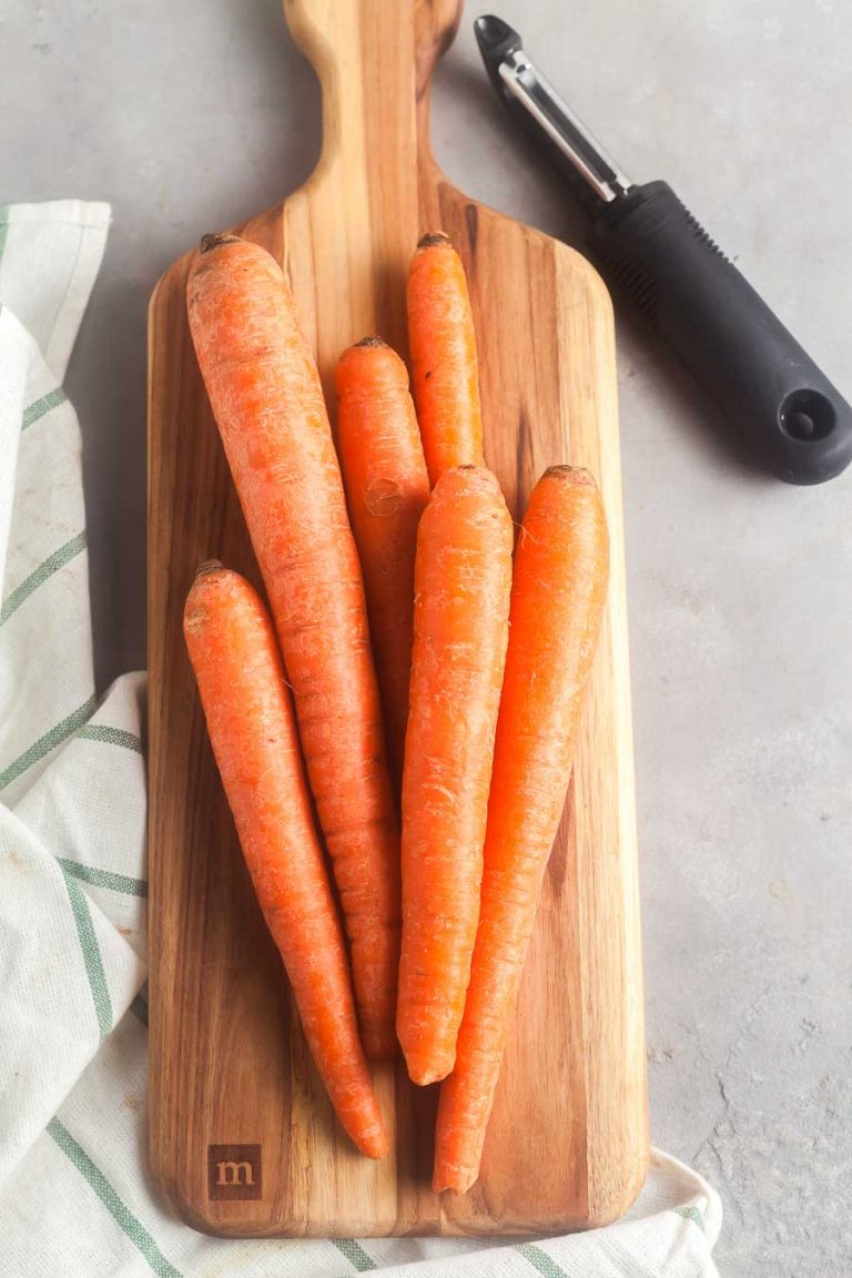 Carrots on a cutting board, ready to be peeled