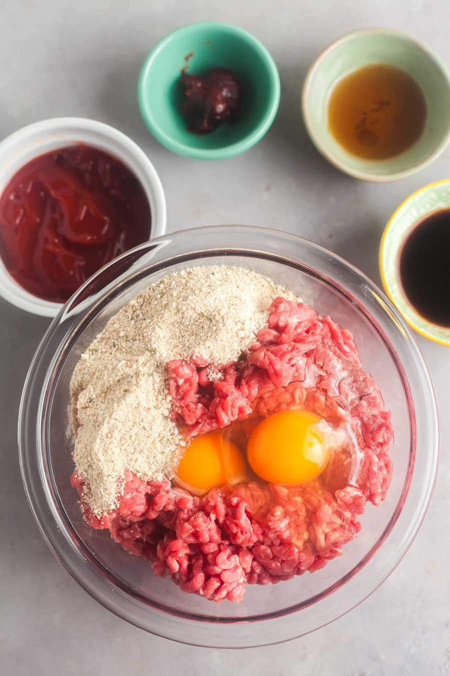 An overhead view of the ingredients to make slow cooker meatloaf. Ground beef, eggs, and breadcrumbs are together in a large bowl, The sauce ingredients are in individual bowls alongside