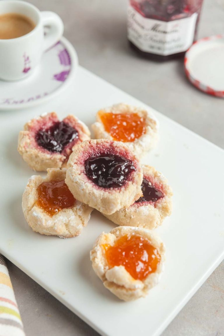 6 almond thumbprint cookies topped with cherry and apricot jam on a white cutting board with a cup of espresso in the background.