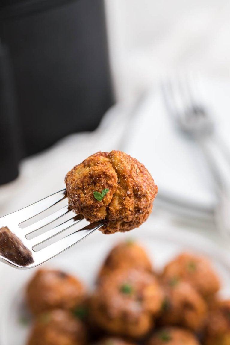 An air fryer chicken meatball on a fork.
