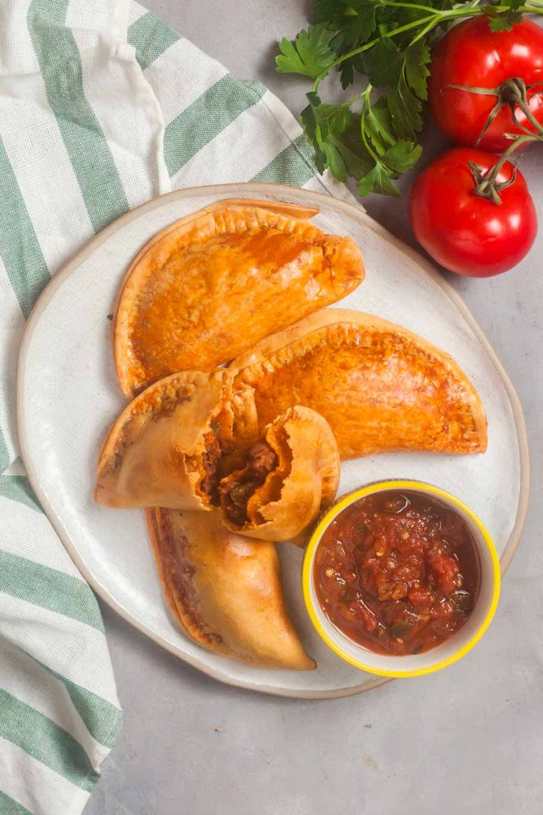 A white platter of air fryer empanadas with a dish of salsa. One empanada is broken open so you can see the chili filling inside.