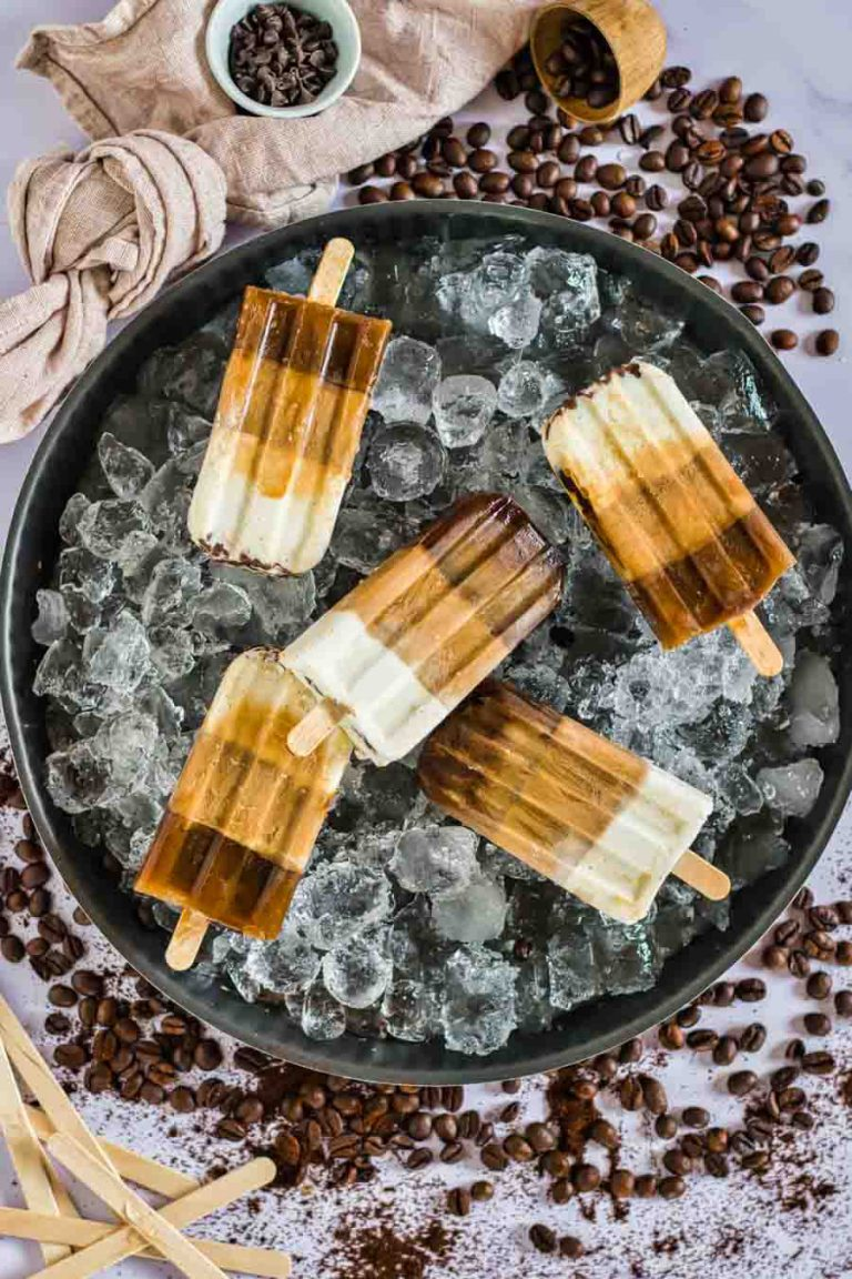 An overhead view of an ice-filled platter layered with low-carb popsicles. Coffee beans and coffee grounds scattered on the background.