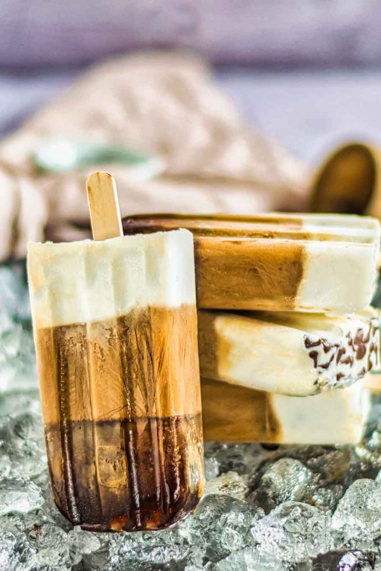 Coffee popsicles stacked on a bed of ice. One popsicle is leaning upright against the stack to show off the three layers of flavor.