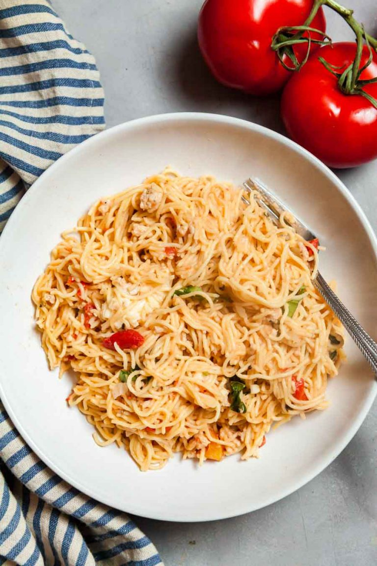 Overhead view of a white plate filled with chicken caprese pasta with a blue stripes napkin and red tomatoes.