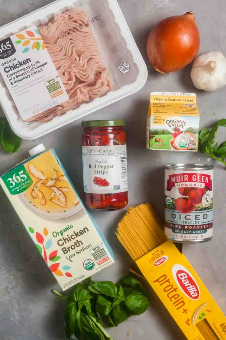 Overhead image depicting ingredients for making chicken caprese pasta include ground chicken, canned tomatoes, roasted red peppers, chicken broth, and fresh basil.