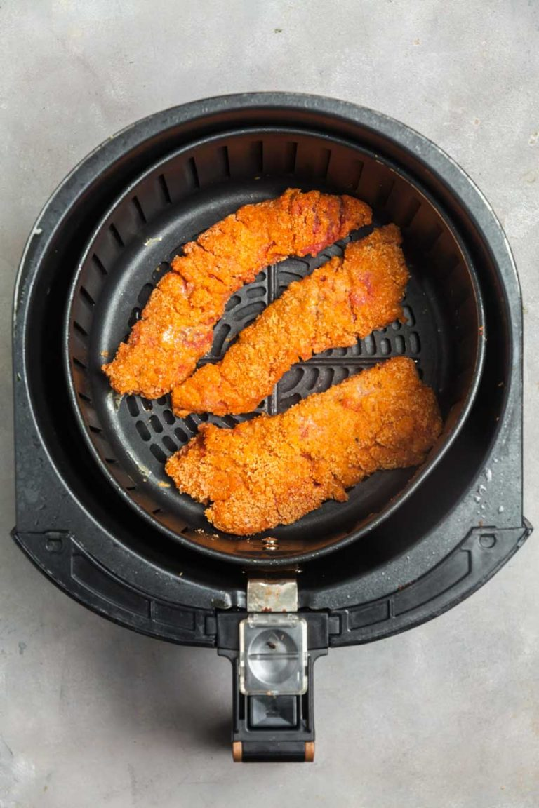 an overhead view of an air fryer backer with three Nashville hot steak fingers inside, ready to be cooked.