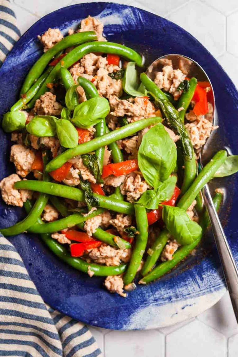 Blue serving dish piled high with basil chicken and green beans.