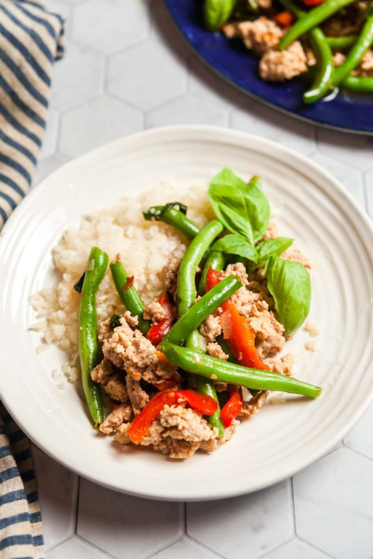 A white plate with a serving of basil chicken and green beans served over cauliflower rice.