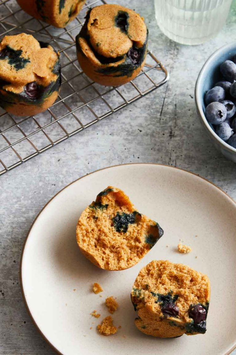 A plate with a whole grain blueberry muffin cut in half and whole muffins in the background.