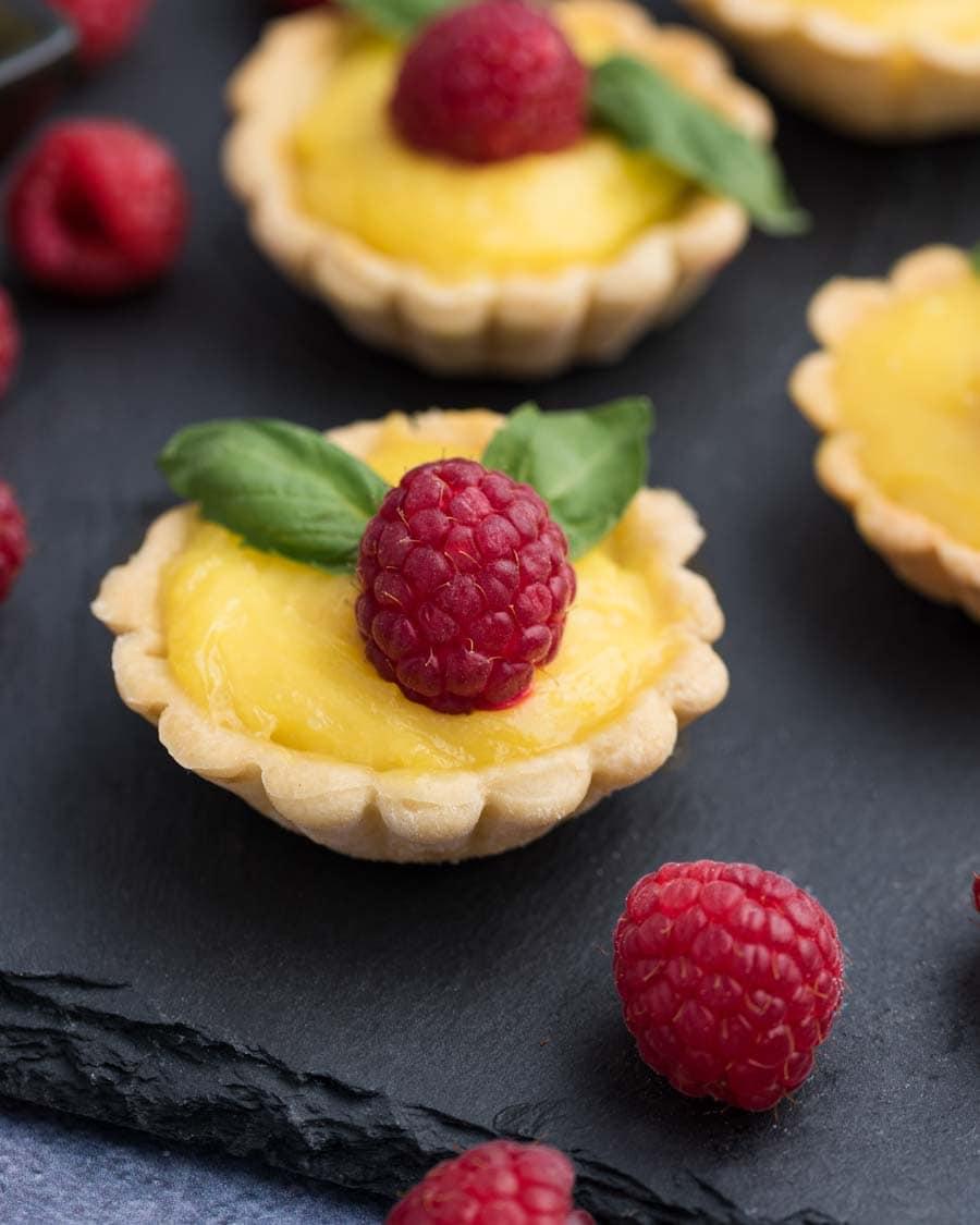 Miniature lemon tarts with fresh raspberries and mint on a slate board.