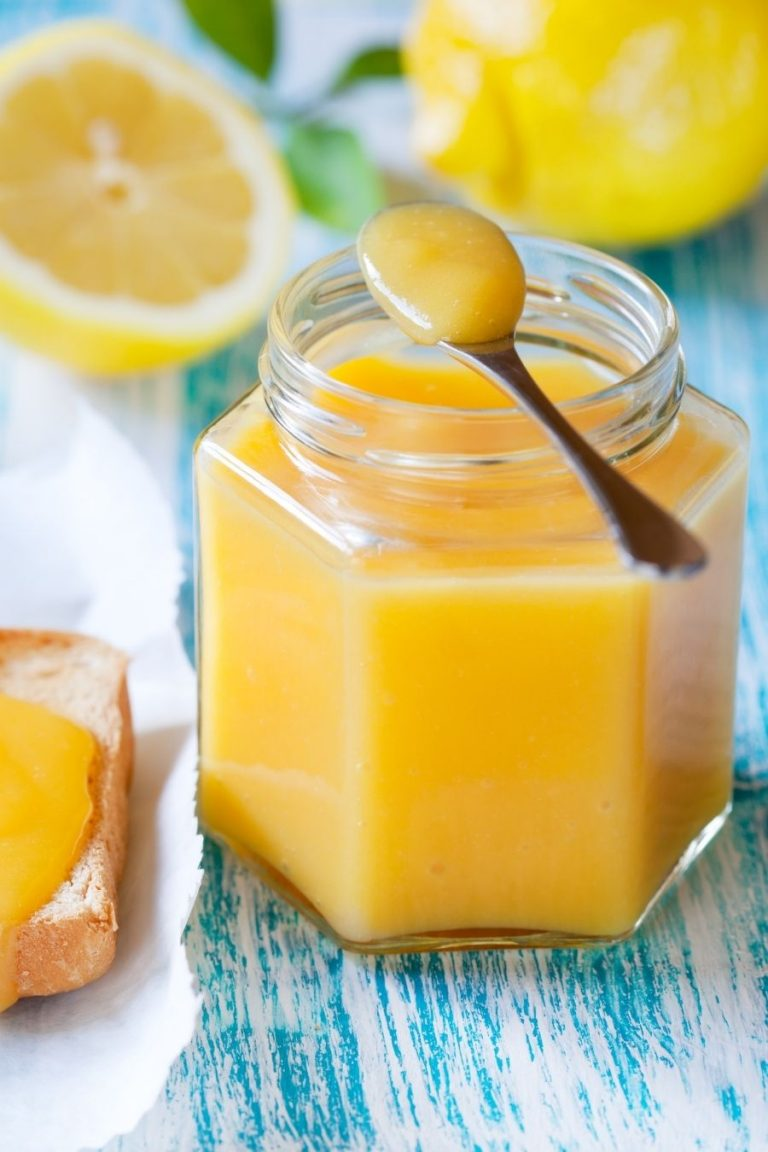 A glass jar of lemon curd on a blue background with cut lemons in the background.