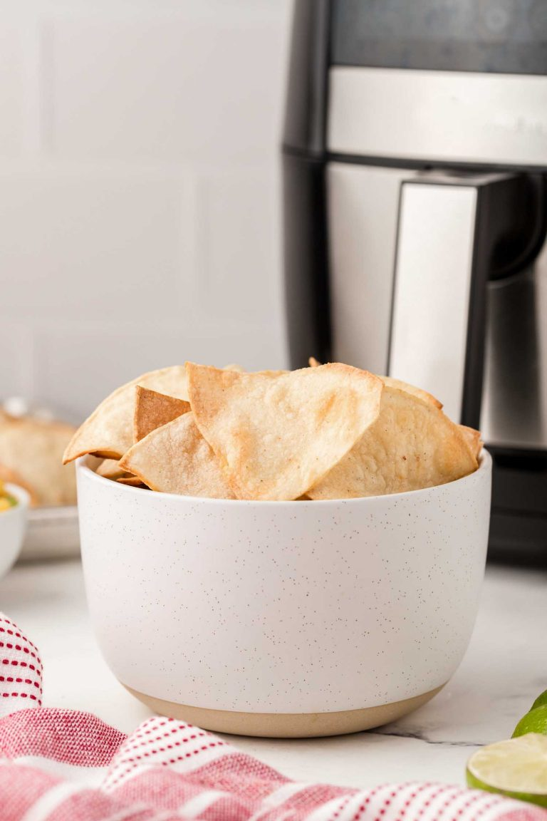 A speckled white bowl of crispy air fryer tortilla chips in front of any air fryer.