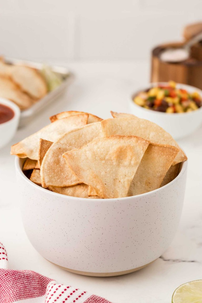 A white bowl of air fried tortilla chips in front of traditional chip accompaniments.