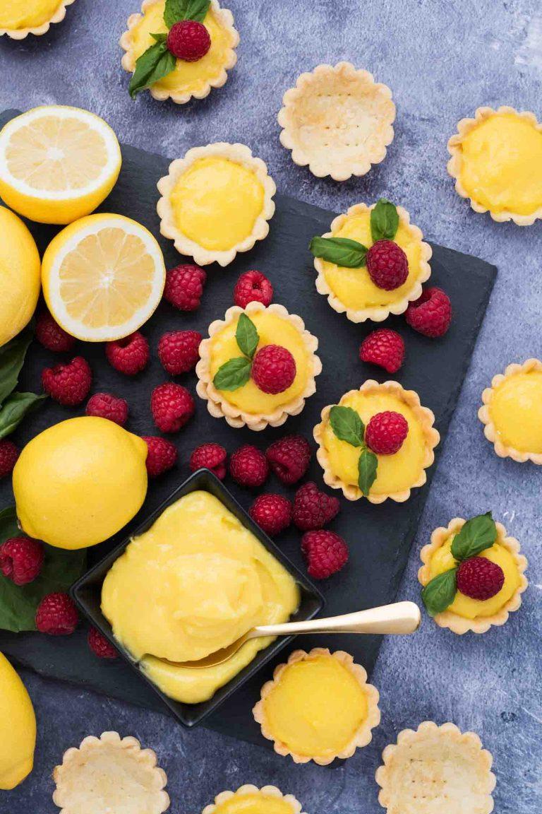 Overhead view of mini lemon tarts with lemon curd and fresh raspberries.