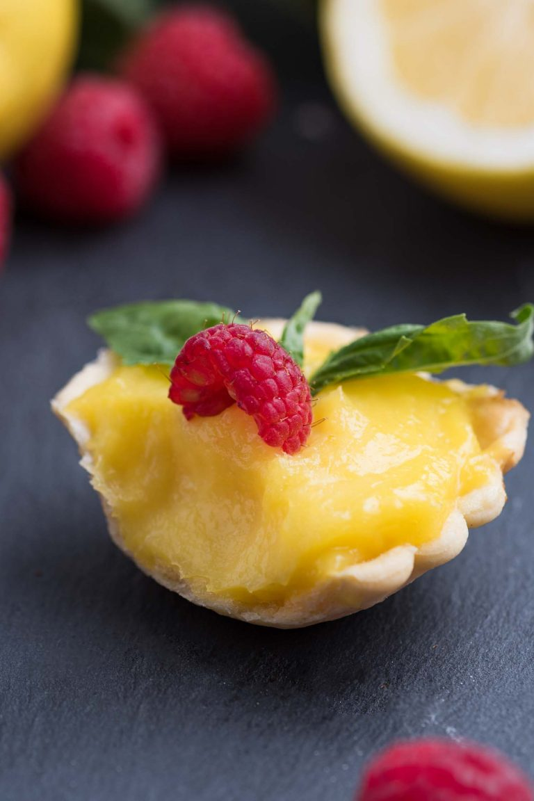 Close up view of a min lemon tartlet with a bite taken out.