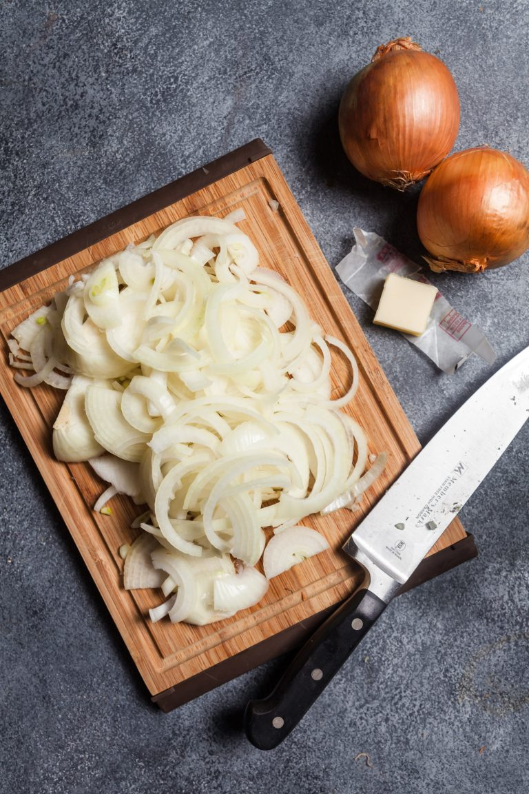 An overhead view of the ingredients needed to make caramelized onions in a slow cooker: just thinly sliced onions and a pat of butter.