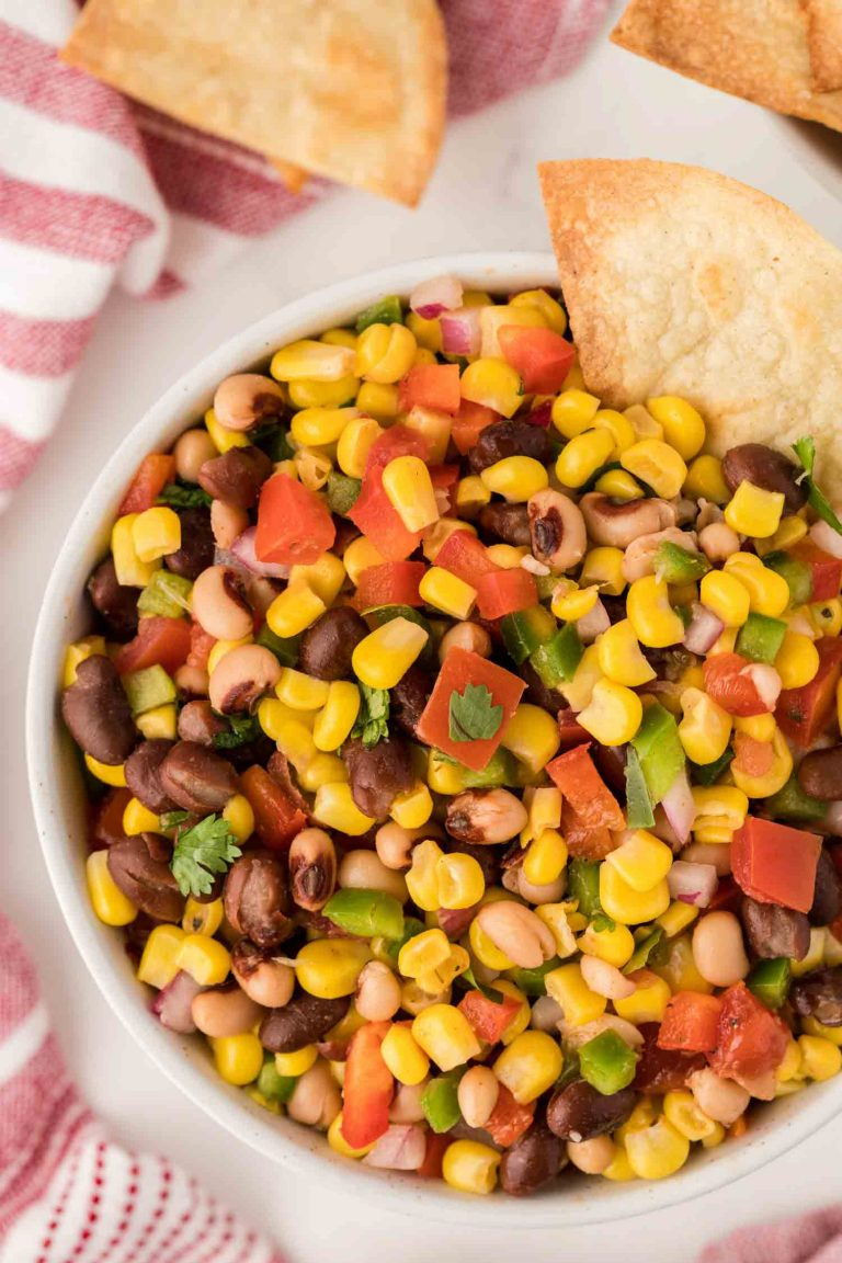 A close-up overhead view of texas caviar, with a tortilla chip digging in.