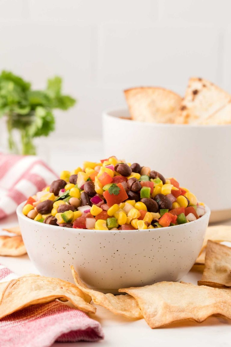 Side view of a bowl filled with vibrant cowboy caviar, surrounded by homemade tortilla chips.